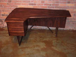 Outstanding Mid-century modern Rosewood desk – designed by Peter Lovig Nielsen – Denmark – design year 1956 – this beauty has incredibly lovely features including a deep rich grain – a unique L shape top a raised lip – dovetailed drawers – handsome brass bar at base along with a locking bar cabinet on the backside with a bookshelf as well -this stunner measures – 58″L x 34″D x 29″H – $2,200