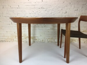 """Exceptional Danish teak dining table with beveled edges Designed by Ole Hald for Gudme Møbelfabrik in the mid-late 1960s. Superb Danish craftsmanship - beautiful deep color and grain, this beauty comes with 2 leaves with same finished edge as the table - it starts as a 48"""" round table and extends with both leaves to 87"""" - (SOLD)"""