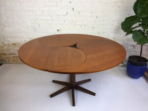 """Exquisite and absolutely exceptional 1960's Danish Modern """"Yin-Yang"""" teak pedestal dining table by furniture designers Ole Gjerløv-Knudsen and Torben Lind. Made by France and Son furniture company - comprised of rich natural teak top and wenge wood pedestal base - made of three interlocking comma-shaped leaves that pivot and lock together. A black lacquered triangular piece fits in the middle of the leaves when all are fully installed, when you remove a leaf the remaining leaves pivot to form a perfect oval of the famed """"yin-yang"""" design, the makers metal button is located underneath the table top(SOLD)"""