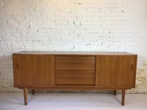 """Gorgeous Quality 1960's teak credenza designed by Nils Jonsson for Hugo Troeds,- Made in Sweden - adjustable shelving on both sides and a center of 4 drawers with the top one showcasing blue felted flatware area that is Nils signature - - dovetailed drawers, rare to find wood runner for the sliding doors - all top tier - this beauty is in very good vintage condition - measures - 71.5""""L x 17""""D x 32""""H (SOLD)"""