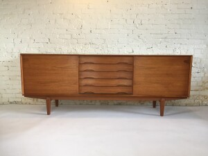 """Impressive high quality Danish Modern teak sideboard designed' by Henry Rosengren Hansen Dyrlund - Made in Denmark - circa 1960's - this statement piece showcases many incredible features including dovetailed wood drawers, tiered shapely drawer fronts, angled inset carved pulls - sculptural carved legs - adjustable shelving on both sides - the grain on this beauty is also to be desired - measures - 86.5""""L x 18.5 """"D x 32.5""""H (SOLD)"""