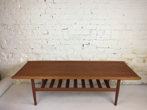 """Handsome MCM Classic teak 2 tier coffee table - the Canadian version of the Danish - Grete Jalk one :) fantastic solid teak curved edge running the length of the table - 2nd tier for your magazines - remotes etc... - newly refinished -this beauty measures - 59""""L x 22.5""""D x 17.5""""H -(SOLD)"""
