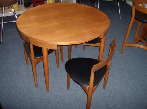 A Mid-century Marvel - one of the greatest designs to come out of Denmark - Designed by Hans Olsen 1952 /manufactured by Frem Rojle - Teak dining table and 4 -3 legged chairs that nest right into the skirt of the table - perfect for small spaces - Nice overall condition - 2 of the 3 legged chair seats have small splits - Super price - (SOLD)